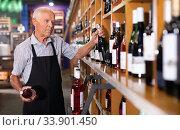 Купить «Confident elderly salesman of wine house arranging wine bottles on shelves rack», фото № 33901450, снято 8 мая 2019 г. (c) Яков Филимонов / Фотобанк Лори