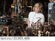 Senior woman chooses rare walking stick at flea market. Стоковое фото, фотограф Яков Филимонов / Фотобанк Лори
