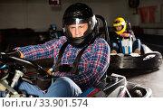 Купить «Male in helmet and other people driving cars for karting in sport club indoor», фото № 33901574, снято 5 июля 2020 г. (c) Яков Филимонов / Фотобанк Лори