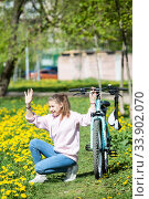 Teenage girl waving with hand to somebody when sitting next to her bicycle in summer park pathway with yellow flowers. Стоковое фото, фотограф Кекяляйнен Андрей / Фотобанк Лори