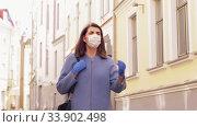 Купить «woman in medical mask and gloves walking in city», видеоролик № 33902498, снято 28 мая 2020 г. (c) Syda Productions / Фотобанк Лори