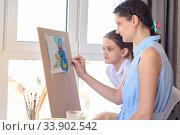 Дочка смотрит как рисует на мольберте мама. Стоковое фото, фотограф Иванов Алексей / Фотобанк Лори