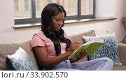 Купить «woman with diary sitting on sofa at home», видеоролик № 33902570, снято 24 мая 2020 г. (c) Syda Productions / Фотобанк Лори