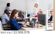 Focused female working with laptop in busy modern office. Стоковое фото, фотограф Яков Филимонов / Фотобанк Лори