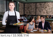 Attractive young waitress with serving tray welcoming in restaurant. Стоковое фото, фотограф Яков Филимонов / Фотобанк Лори