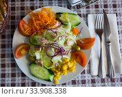 Купить «Mix salad with vegetables, boiled carrot, corn and lettuce at plate», фото № 33908338, снято 11 июля 2020 г. (c) Яков Филимонов / Фотобанк Лори