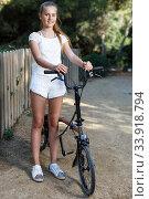 Teen girl standing near fence with bike ready to go on park ride. Стоковое фото, фотограф Яков Филимонов / Фотобанк Лори