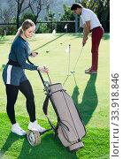 Купить «Woman golfer deciding on right club while her male partner hitting ball», фото № 33918846, снято 6 августа 2020 г. (c) Яков Филимонов / Фотобанк Лори