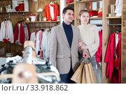 Купить «Smiling couple is satisfied of purchases and walking with package», фото № 33918862, снято 12 марта 2018 г. (c) Яков Филимонов / Фотобанк Лори