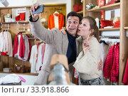 Купить «Smiling couple is satisfied of purchases and taking selfie», фото № 33918866, снято 12 марта 2018 г. (c) Яков Филимонов / Фотобанк Лори