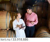 Купить «Sommelier advising male customer in winery cellar», фото № 33918886, снято 21 сентября 2016 г. (c) Яков Филимонов / Фотобанк Лори
