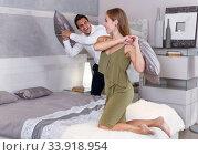 Купить «Couple having pillow fight in bedroom», фото № 33918954, снято 24 сентября 2018 г. (c) Яков Филимонов / Фотобанк Лори