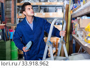 Купить «Man in unifom is using ladder to reach the top shelves in the building store.», фото № 33918962, снято 26 июля 2017 г. (c) Яков Филимонов / Фотобанк Лори