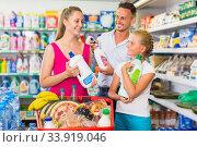Купить «Family of three are selecting detergents», фото № 33919046, снято 11 июля 2017 г. (c) Яков Филимонов / Фотобанк Лори