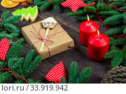 Gift in craft paper with a gingerbread house, in the photo a fir tree and candles. Стоковое фото, фотограф Константин Лабунский / Фотобанк Лори