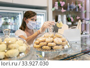 Купить «Female bakery owner preparing an order and wearing a protective mask due to the corona virus pandemic.», фото № 33927030, снято 7 мая 2020 г. (c) easy Fotostock / Фотобанк Лори