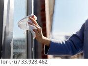 Купить «woman cleaning door handle with wet wipe», фото № 33928462, снято 30 апреля 2020 г. (c) Syda Productions / Фотобанк Лори