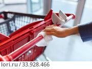 Купить «hand cleaning shopping cart handle with wet wipe», фото № 33928466, снято 30 апреля 2020 г. (c) Syda Productions / Фотобанк Лори