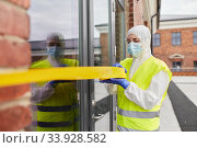 Купить «healthcare worker sealing door with caution tape», фото № 33928582, снято 24 апреля 2020 г. (c) Syda Productions / Фотобанк Лори