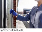 Купить «woman in protective glove trying to open door», фото № 33928598, снято 30 апреля 2020 г. (c) Syda Productions / Фотобанк Лори