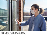Купить «woman in mask cleaning door handle with wet wipe», фото № 33928602, снято 30 апреля 2020 г. (c) Syda Productions / Фотобанк Лори