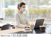 Купить «woman in mask with laptop working at home office», фото № 33928686, снято 27 марта 2020 г. (c) Syda Productions / Фотобанк Лори