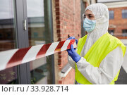 Купить «healthcare worker sealing door with caution tape», фото № 33928714, снято 24 апреля 2020 г. (c) Syda Productions / Фотобанк Лори