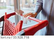 Купить «hand cleaning shopping cart handle with wet wipe», фото № 33928718, снято 30 апреля 2020 г. (c) Syda Productions / Фотобанк Лори