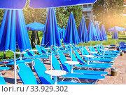 Купить «blue umbrellas and sun beds near the pool in the summer resort», фото № 33929302, снято 5 июля 2017 г. (c) Nataliia Zhekova / Фотобанк Лори