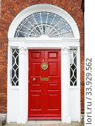 A red door in Dublin, Ireland (2019 год). Стоковое фото, фотограф Nataliia Zhekova / Фотобанк Лори