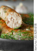 baked homemade sausage with spices and herbs, close up. Spiral grilled sausage. Стоковое фото, фотограф Nataliia Zhekova / Фотобанк Лори