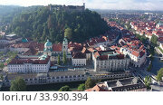 Купить «Panoramic aerial view of Ljubljana cityscape on banks of river Ljubljanica in sunny autumn morning, Slovenia», видеоролик № 33930394, снято 4 сентября 2019 г. (c) Яков Филимонов / Фотобанк Лори