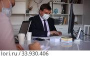 Купить «Portrait of confident manager wearing medical mask and protective gloves working with female colleague in office. New life reality during coronavirus pandemic», видеоролик № 33930406, снято 12 мая 2020 г. (c) Яков Филимонов / Фотобанк Лори