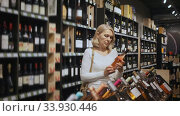 Positive middle aged blonde woman choosing bottled wine in modern wineshop. Стоковое видео, видеограф Яков Филимонов / Фотобанк Лори
