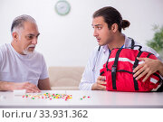 Young male doctor visiting old male patient at home. Стоковое фото, фотограф Elnur / Фотобанк Лори