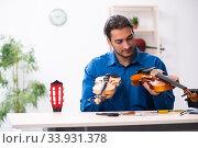 Купить «Young male repairman repairing violin», фото № 33931378, снято 25 октября 2019 г. (c) Elnur / Фотобанк Лори