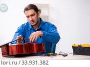 Young male repairman repairing cello. Стоковое фото, фотограф Elnur / Фотобанк Лори