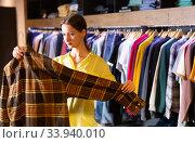 Купить «Satisfied woman chooses fashionable checkered shirt», фото № 33940010, снято 12 июля 2020 г. (c) Яков Филимонов / Фотобанк Лори