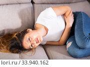 Latino woman experiencing pain in the stomach. Стоковое фото, фотограф Яков Филимонов / Фотобанк Лори