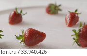 Купить «Ripe red strawberry fruit falls into the center of a plate of water with splashes and drops of water. A few berries lie on the white plate. Slow motion. Out of focus. Full HD video, 240fps,1080p.», видеоролик № 33940426, снято 10 июля 2020 г. (c) Ярослав Данильченко / Фотобанк Лори