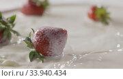 Купить «Milk splash on a ripe red strawberry fruit, which lies on a white plate with milk. Slow motion. A few berries lie on the white plate. Soft focus, close-up. Full HD video, 240fps,1080p.», видеоролик № 33940434, снято 12 июля 2020 г. (c) Ярослав Данильченко / Фотобанк Лори