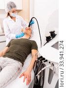 Woman cosmetologist giving facial electroporation procedure to male. Стоковое фото, фотограф Яков Филимонов / Фотобанк Лори