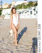 Купить «Beauty female in swimsuit with hat posing near buildings at sea shore», фото № 33941338, снято 10 июля 2018 г. (c) Яков Филимонов / Фотобанк Лори