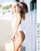 Купить «Sexy girl in swimsuit and hat playfully posing hotel wall at sea shore», фото № 33941342, снято 10 июля 2018 г. (c) Яков Филимонов / Фотобанк Лори