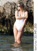Купить «Young female in swimsuit and sunglasses near stones at sea shore», фото № 33941350, снято 10 июля 2018 г. (c) Яков Филимонов / Фотобанк Лори