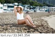 Купить «Female in swimsuit taking sunbath at sand at sea shore on sunny day», фото № 33941354, снято 10 июля 2018 г. (c) Яков Филимонов / Фотобанк Лори