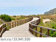Купить «Wooden empty board walk leading through sandy dunes to Mediterranean Sea and beach of Los Arenales del Sol or Arenals del Sol. Costa Blanca, Europe, Spain. Espana», фото № 33941930, снято 2 июня 2020 г. (c) Alexander Tihonovs / Фотобанк Лори
