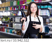Female hairdresser in apron holding blow dryer and hair cutters in shop. Стоковое фото, фотограф Яков Филимонов / Фотобанк Лори