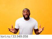 Купить «Portrait of african american man with hands raised in shock and disbelief. Isolated over yellow background», фото № 33949058, снято 10 июля 2020 г. (c) easy Fotostock / Фотобанк Лори