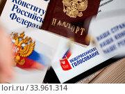 Купить «Брошюра Конституции Российской Федерации паспорт и гаджет с открытым заявлением на дистанционное участие в общероссийском голосовании 1 июля 2020 года лежат на деревянном столе», фото № 33961314, снято 9 июня 2020 г. (c) Николай Винокуров / Фотобанк Лори